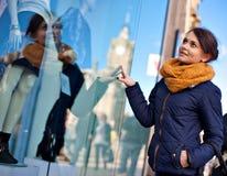 La ragazza sta esaminando la finestra del negozio immagini stock libere da diritti