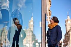 La ragazza sta esaminando la finestra del negozio immagini stock