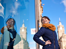 La ragazza sta esaminando la finestra del negozio immagine stock