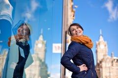 La ragazza sta esaminando la finestra del negozio immagine stock libera da diritti
