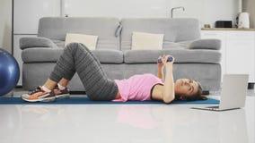 La ragazza sta facendo il compito mentre faceva gli esercizi dal computer portatile archivi video