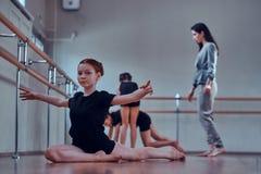 La ragazza sta facendo strechening mentre i suoi altri compagni di classe che fanno gli esercizi con l'insegnante fotografia stock