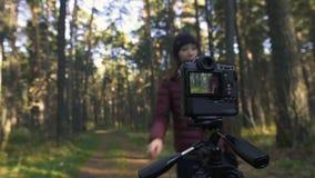 La ragazza sta facendo un selfie dentro in foglie gialle nel parco di autunno Macchina fotografica sul treppiedi archivi video