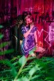 La ragazza sta facendo una pausa la parete con la cannabis in sue mani Fotografia Stock
