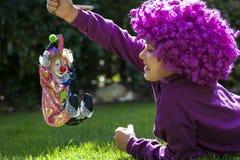 La ragazza sta giocando con un pagliaccio Fotografie Stock