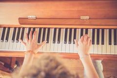 La ragazza sta giocando il piano a casa, vista dell'angolo alto, fondo confuso fotografie stock
