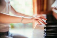 La ragazza sta giocando il piano a casa, vista dell'angolo alto, fondo confuso immagine stock libera da diritti