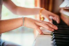La ragazza sta giocando il piano a casa, vista dell'angolo alto, fondo confuso fotografie stock libere da diritti
