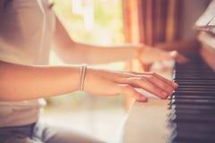 La ragazza sta giocando il piano a casa, vista dell'angolo alto, fondo confuso fotografia stock
