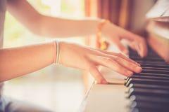 La ragazza sta giocando il piano a casa, vista dell'angolo alto, fondo confuso immagine stock