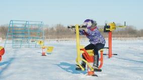 La ragazza sta giocando l'attrezzatura di forma fisica per 6 anni nel cortile della scuola stock footage