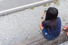 La ragazza sta giocando lo smartphone allo stadio Fotografia Stock Libera da Diritti