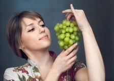 La ragazza sta guardando sull'uva Immagini Stock