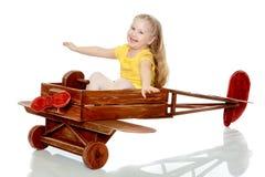 La ragazza sta guidando un aereo del giocattolo Fotografia Stock
