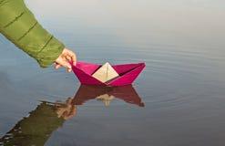 La ragazza sta lanciando una barca di carta rossa, crogiolo di carta di primo piano fotografia stock libera da diritti