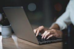 La ragazza sta lavorando tardi nell'ufficio scuro con un computer portatile Giovane bella ragazza della donna di affari in uffici fotografie stock libere da diritti