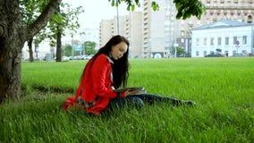 La ragazza sta leggendo nel parco video d archivio