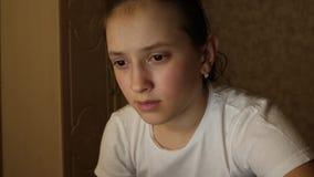 La ragazza sta leggendo un libro elettronico in computer portatile alla notte Il bambino si siede nella rete sociale nel email de video d archivio