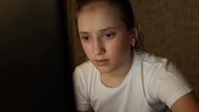 La ragazza sta leggendo un libro elettronico in computer portatile alla notte Il bambino si siede nella rete sociale nel email de stock footage