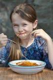 La ragazza sta mangiando gli spaghetti Fotografie Stock