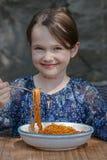 La ragazza sta mangiando gli spaghetti Immagine Stock