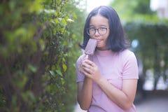 La ragazza sta mangiando il gelato Immagini Stock