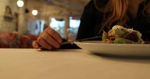 La ragazza sta mangiando l'insalata di verdure facendo uso della forcella ed il coltello al caffè stock footage
