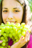 La ragazza sta mangiando l'uva Fotografia Stock