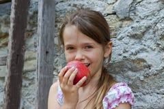 La ragazza sta mangiando la frutta Fotografie Stock Libere da Diritti