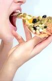 La ragazza sta mangiando la pizza Immagini Stock