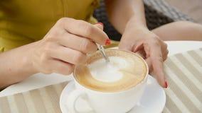 La ragazza sta mescolando il cappuccino con un cucchiaio in una tazza bianca stock footage