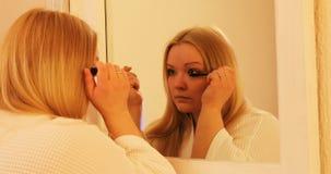 La ragazza sta mettendo la mascara sopra davanti al grande specchio stock footage