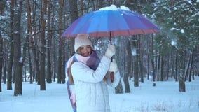 La ragazza sta nel legno e gira l'ombrello con cui cade nella neve stock footage
