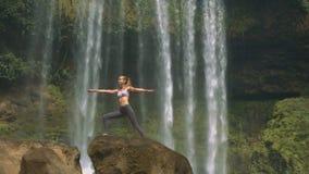 La ragazza sta nella posa di yoga su roccia marrone alla cascata archivi video