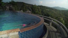 La ragazza sta nuotando nello stagno in cima ad un video del metraggio delle azione della montagna stock footage