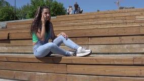 La ragazza sta parlando su un telefono cellulare mentre si sedeva su un banco nel parco che ha un buon umore 4K video d archivio