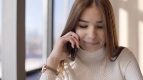 La ragazza sta parlando sul telefono in un caffè archivi video