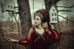 La ragazza sta posando in un vestito rosso con l'acconciatura creativa fotografia stock libera da diritti