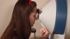 La ragazza sta premendo il tasto quando guarda gli oggetti dentro il dispositivo per il computer perimetry video d archivio