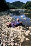 La ragazza sta prendendo il sole sotto il sole Fotografia Stock Libera da Diritti