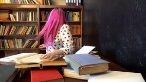 La ragazza sta preparando per l'esame nei libri di lettura delle biblioteche archivi video