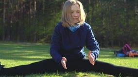 La ragazza sta preparandosi nel parco sul prato inglese stock footage