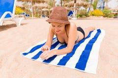 La ragazza sta rilassandosi sull'asciugamano sulla sabbia alla spiaggia e sta applicando la lozione del sole sulla sua mano immagine stock