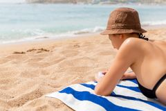 La ragazza sta rilassandosi sull'asciugamano sulla sabbia alla spiaggia e sta applicando la lozione del sole sulla sua mano fotografia stock