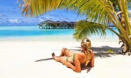 La ragazza sta rilassandosi sulla spiaggia dell'oceano Fotografia Stock Libera da Diritti