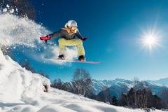 La ragazza sta saltando con lo snowboard Immagine Stock