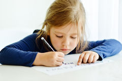 La ragazza sta scrivendo Immagine Stock