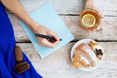 La ragazza sta scrivendo i piani per il futuro Tè e croissant caldi Fotografia Stock