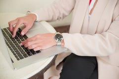 La ragazza sta scrivendo su un computer portatile immagini stock