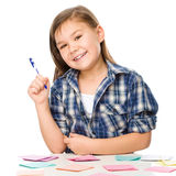 La ragazza sta scrivendo sugli autoadesivi di colore facendo uso della penna Fotografia Stock Libera da Diritti
